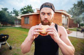 Homme ahuri qui tient un burger